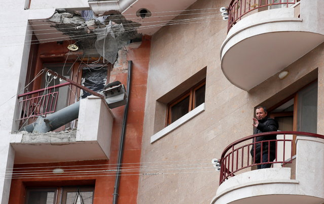 A local resident speaks as he stands near a missile case on a balcony of a residential building in Stepanakert in the region of Nagorno-Karabakh, November 16, 2020. (Photo by Reuters/Stringer)