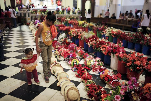 Girls look at offerings left by devotees to celebrate the Day of the Virgin of Guadalupe inside the Basilica of Guadalupe in San Salvador, El Salvador December 11, 2015. (Photo by Jose Cabezas/Reuters)