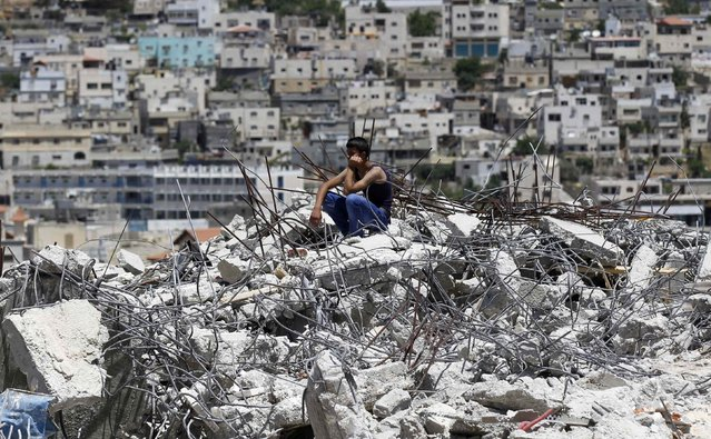 A Palestinian sits on top of the rubble of a house under construction after it was demolished by Israeli bulldozers at Al-Aroub refugee camp, near the West Bank City of Hebron April 30, 2014.(Photo by Ammar Awad/Reuters)