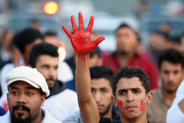 An Iraqi man displays his hand, painted red to symbolize blood, during a demonstration against the ongoing violence and lack of security in the southern city of Basra on December 17, 2015. (Photo by Haidar Mohammed Ali/AFP Photo)
