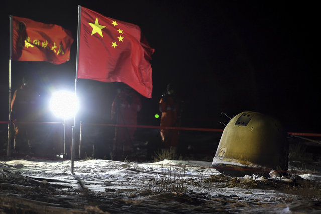 In this photo released by Xinhua News Agency, recovery crew members film the capsule of the Chang'e 5 probe after its successful landed in Siziwang district, north China's Inner Mongolia Autonomous Region on Thursday, December 17, 2020. A Chinese lunar capsule returned to Earth on Thursday with the first fresh samples of rock and debris from the moon in more than 40 years. (Photo by Ren Junchuan/Xinhua via AP Photo)