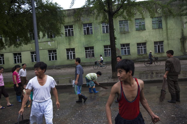 North Koreans clean a street after a heavy rainfall in Kaesong, North Korea on Monday, July 22, 2013. (Photo by David Guttenfelder/AP Photo)