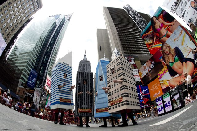 A barbershop quartet named The Broadscrapers, costumed in 10-foot-tall replicas of the Citicorp, Empire State, Freedom Tower and Chysler Building in Times Square in New York, on July 25, 2013. (Photo by Don Emmert/AFP Photo)