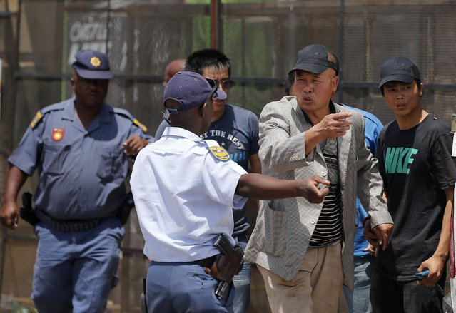 A foreign shop owner gestures as he talks to a police officer after their shops were looted during service delivery protests in Mohlakeng, west of Johannesburg, February 4, 2015. (Photo by Siphiwe Sibeko/Reuters)