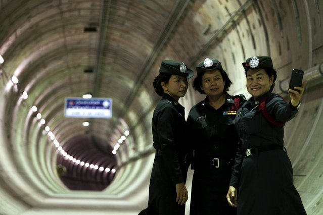 Policewomen take a picture inside a tunnel under the Chao Phraya river at a Mass Rapid Transit subway station in Bangkok, Thailand, December 14, 2015. (Photo by Athit Perawongmetha/Reuters)