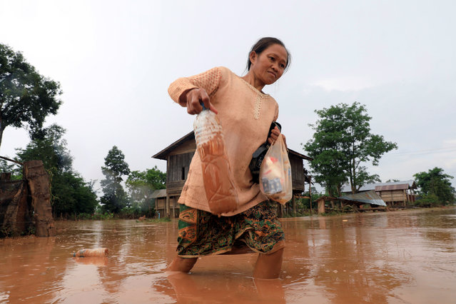 A woman walks on a road during the flood after the Xepian-Xe Nam Noy hydropower dam collapsed in Attapeu province, Laos on July 26, 2018. (Photo by Soe Zeya Tun/Reuters)