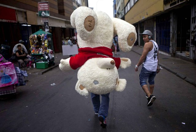 A vendor carries an oversized teddy bear to be sold as a Valentine's Day gift, in the central market of Lima, Peru, Wednesday, February 4, 2015. (Photo by Esteban Felix/AP Photo)