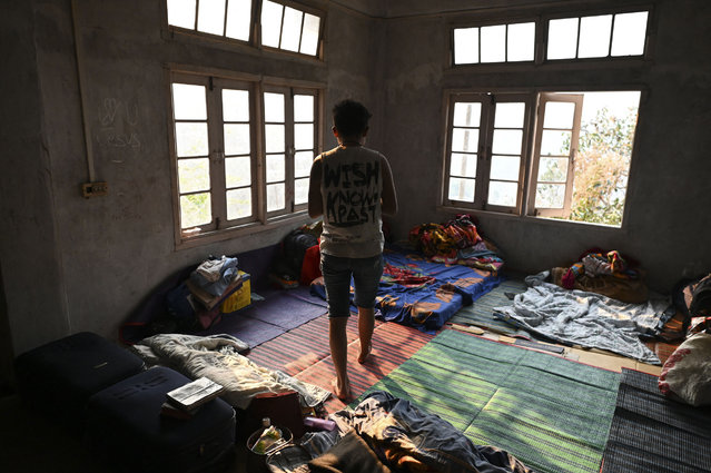 """A Myanmarese policeman, who fled Myanmar and crossed illegally to India, stands in a temporary shelter at an undisclosed location in India's northeastern state of Mizoram on March 13, 2021. Scores of Myanmar policemen and their families have now fled to India, security officials said on March 12, with one officer telling AFP that the authorities are """"beating and torturing"""" protestors. (Photo by Sajjad Hussain/AFP Photo)"""
