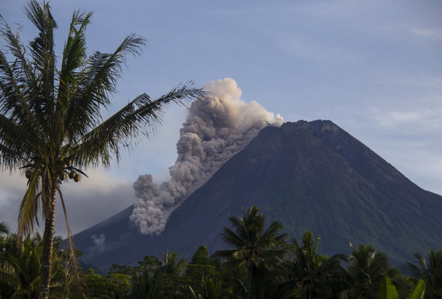 Mount Merapi releases volcanic materials down its slope during an eruption in Sleman, Indonesia, Saturday, March 27, 2021. Indonesia's most volatile volcano was erupting again Saturday, releasing plumes of ash high into the air and sending streams of lava and debris down its slopes. No casualties were reported. (Photo by Slamet Riyadi/AP Photo)