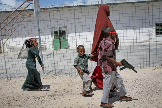 In this photo taken Saturday, October 4, 2014, a Somali mother walks with her children, one carrying a plastic toy gun, towards an area with children's toys to play with at the Mogadishu Guest House, in Mogadishu, Somalia. (Photo by Farah Abdi Warsameh/AP Photo)