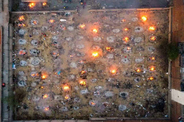 In this aerial picture taken on April 26, 2021, burning pyres of victims who lost their lives due to the Covid-19 coronavirus are seen at a cremation ground in New Delhi. (Photo by Jewel Samad/AFP Photo)