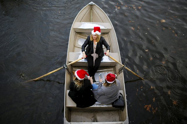 Women enjoy a warm day on a boat at the lake in Central Park, New York December 25, 2015. (Photo by Eduardo Munoz/Reuters)