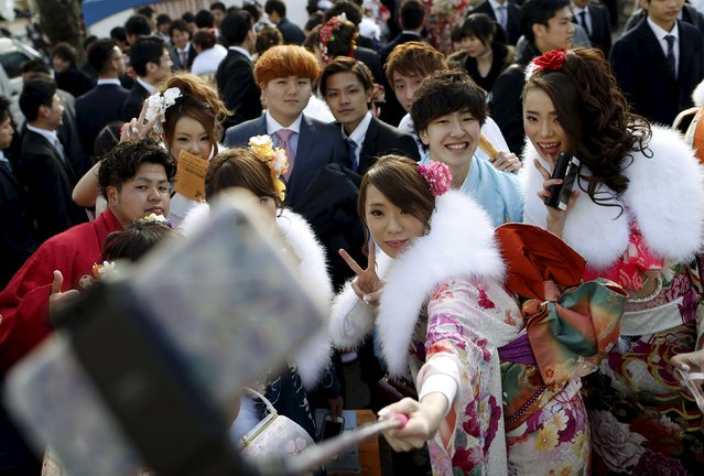 Japanese women wearing kimonos take selfie pictures during their Coming of Age Day celebration ceremony at an amusement park in Tokyo January 11, 2016. (Photo by Yuya Shino/Reuters)