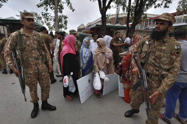 Pakistani troops stand guard while election staff wait for transport after collecting ballot boxes and polling material from a distribution center in Rawalpindi, Pakistan, Tuesday, July 24, 2018. As Pakistan prepares to make history Wednesday by electing a third straight civilian government, rights activists, analysts and candidates say the campaign has been among its dirtiest ever, imperiling the country's wobbly transition to democratic rule. (Photo by Anjum Naveed/AP Photo)