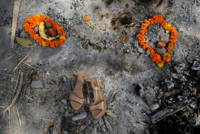 Flower garlands, fruits and a pair of sandals of a woman who died from the coronavirus disease (COVID-19), are placed by her relatives on the spot where she was cremated, as part of a ritual at a crematorium in New Delhi, India, April 30, 2021. (Photo by Adnan Abidi/Reuters)