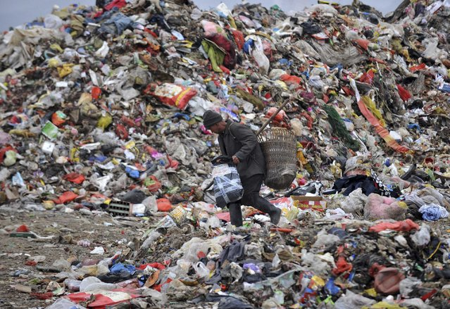 A cleaner works at a dump site in Guiyang, Guizhou province, February 21, 2015. (Photo by Reuters/Stringer)