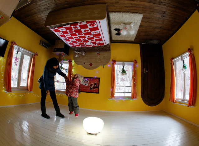 People visit an upside down house, constructed as an attraction for local residents and tourists and located at the Royev Ruchey Park of Flora and Fauna in the suburbs of Krasnoyarsk, Russia, December 7, 2016. (Photo by Ilya Naymushin/Reuters)