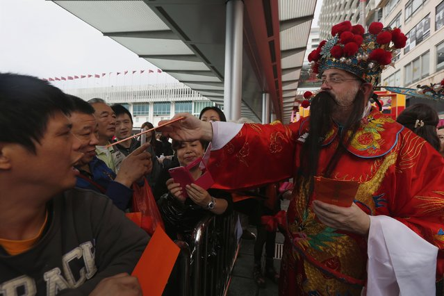 A performer dressed as Cai Shen or God of Wealth, offers red packets to spectators during a Chinese New Year celebration at a shopping mall in Hong Kong February 23, 2015. (Photo by Bobby Yip/Reuters)