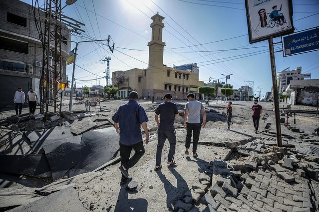 Palestinians inspect a destroyed street after an Israeli strike in Gaza City, 13 May 2021. In response to days of violent confrontations between Israeli security forces and Palestinians in Jerusalem, various Palestinian militants factions in Gaza launched rocket attacks since 10 May that killed at least six Israelis to date. Gaza Strip's health ministry said that at least 65 Palestinians, including 13 children, were killed in the recent retaliatory Israeli airstrikes. Hamas confirmed the death of Bassem Issa, its Gaza City commander, during an airstrike. (Photo by Mohammed Saber/EPA/EFE)