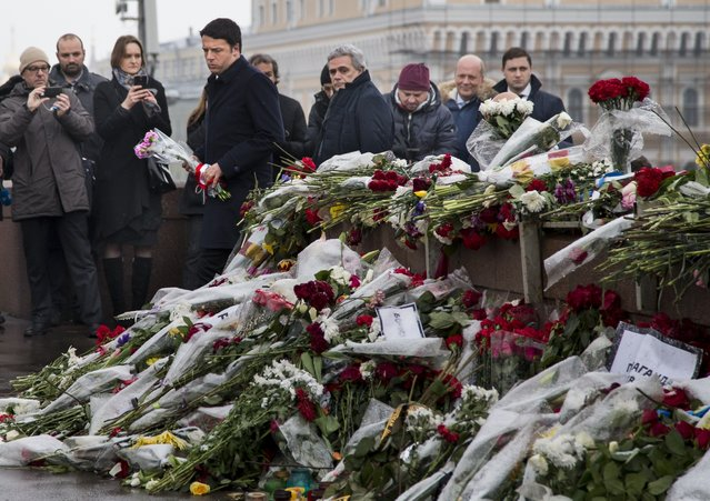 Italian Prime Minister Matteo Renzi, fourth left, pays respects at the place where Boris Nemtsov, a charismatic Russian opposition leader and sharp critic of President Vladimir Putin, was gunned down on Feb. 27, near the Kremlin in Moscow, Russia, Thursday, March 5, 2015. (AP Photo/Alexander Zemlianichenko)