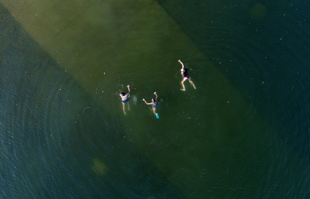 An aerial view shows youths swimming in the Yenisei River on a hot summer day, with the air temperature at about 30 degrees Celsius (86 degrees Fahrenheit), outside Krasnoyarsk, Russia August 17, 2018. (Photo by Ilya Naymushin/Reuters)