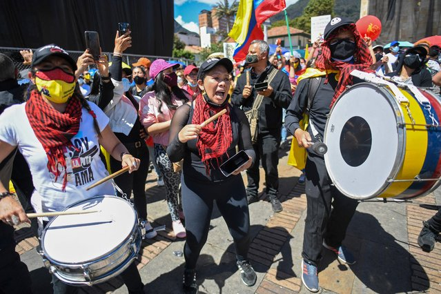 """People play drums as they demonstrate against the government of Colombian President Ivan Duque outside the Congress building in Bogota, on June 2, 2021. Colombian protesters made cautious overtures towards the government Tuesday in talks seeking to end weeks of violent social unrest that has left dozens of people dead and hundreds injured. The National Strike Committee, which represents labour unions, students and indigenous peoples, among others, said there were """"approaches for lifting"""" road blockades that have hamstrung transport for weeks on end, particularly in the country's south. (Photo by Juan Barreto/AFP Photo)"""