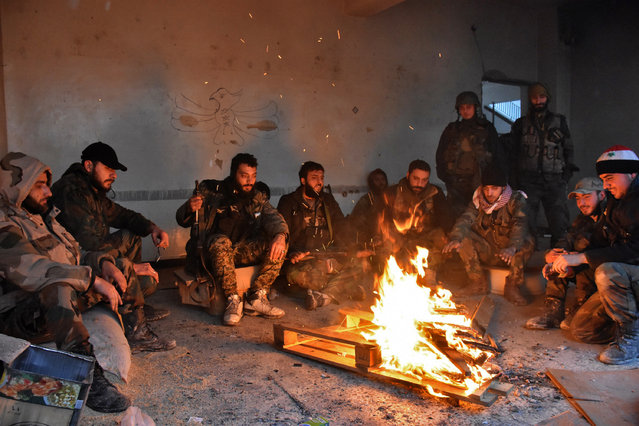 Syrian pro-government forces rest by a fire as they advance in the Jisr al-Haj neighbourhood during the ongoing military operation to retake remaining rebel-held areas in the northern embattled city of Aleppo on December 14, 2016. Shelling and air strikes sent terrified residents running through the streets of Aleppo as a deal to evacuate rebel districts of the city was in danger of falling apart. (Photo by George Ourfalian/AFP Photo)