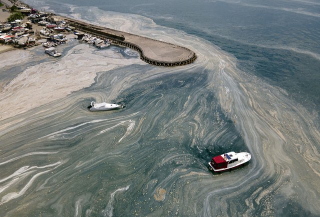 """In an aerial photo, boats are seen near the Caddebostan shore, on the Asian side of Istanbul, Monday, June 7, 2021, with a huge mass of marine mucilage, a thick, slimy substance made up of compounds released by marine organisms, in Turkey's Marmara Sea. Turkey's President Recep Tayyip Erdogan promised Saturday to rescue the Marmara Sea from an outbreak of """"sea snot"""" that is alarming marine biologists and environmentalists.(Photo by Kemal Aslan/AP Photo)"""