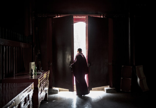 A Tibetan Buddhist monk waits inside a temple before taking  part in the Beating Ghosts ritual at the Lama Temple, or Yonghegong on March 19, 2015 in Beijing, China. The ritual is held on the the 29th day of the first month after Losar, or New Year and is meant to expel evil spirits. (Photo by Kevin Frayer/Getty Images)