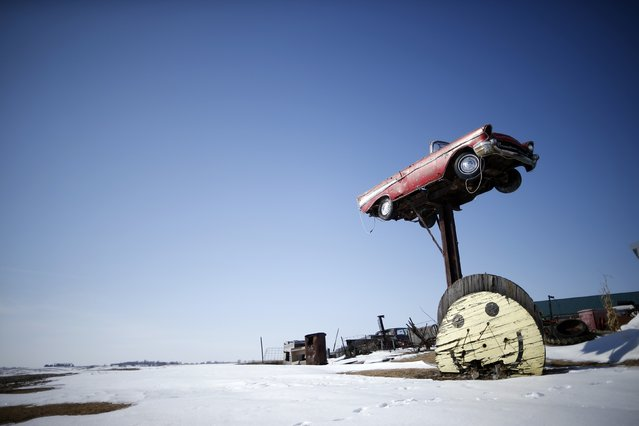 An antique car is seen on top of a post at an auto dealer in West Branch, Iowa, March 6, 2015. (Photo by Jim Young/Reuters)