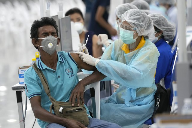 A health worker administers a dose of the AstraZeneca COVID-19 vaccine at the Central Vaccination Center in Bangkok, Thailand, Wednesday, July 14, 2021. Health authorities in Thailand said Wednesday they will seek to  put limits on the export of locally produced AstraZeneca vaccine, as the country's supplies of COVID-19 vaccines are falling short of what is needed for its own population. (Photo by Sakchai Lalit/AP Photo)