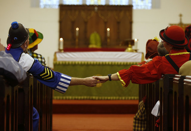 Clowns sit in the pews and hold hands across the aisle of the All Saints Church during the Grimaldi clown service in Dalston, north London, February 7, 2016. (Photo by Peter Nicholls/Reuters)