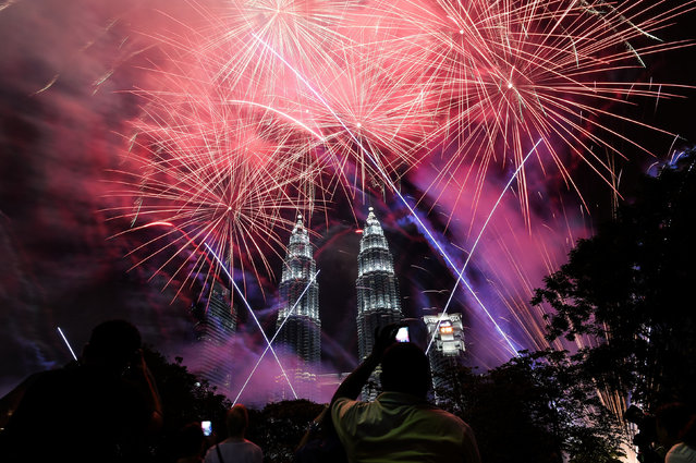 Fireworks illuminate the sky near Malaysia' s landmark Petronas Twin Towers during the New Year celebrations in Kuala Lumpur on January 1, 2017. (Photo by Mohd Rasfan/AFP Photo)