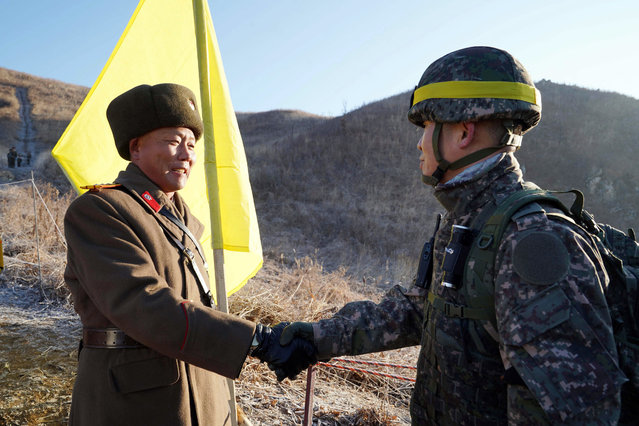 In this photo provided by South Korea Defense Ministry, South Korean army Col. Yun Myung-shick, right, shakes hands with North Korean army Lt. Col. Ri Jong Su before crossing the Military Demarcation Line inside the Demilitarized Zone (DMZ) to inspect the dismantled North Korean guard post in the central section of the inter-Korean border in Cheorwon, Wednesday, December 12, 2018. Dozens of North and South Korean soldiers crossed over the world's most heavily armed border Wednesday as they inspected the sites of their rival's front-line guard posts to verify they'd been removed, part of inter-Korean engagement efforts that come amid stalled U.S.-North Korea nuclear disarmament talks. (Photo by South Korea Defense Ministry via AP Photo)