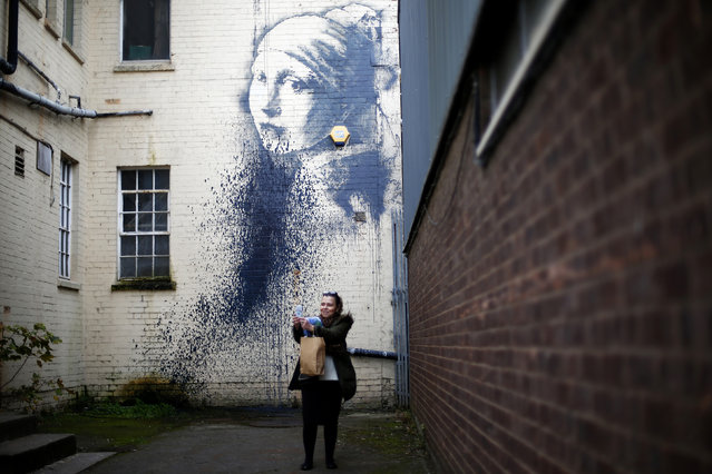 """A woman photographs herself with a piece of street art attributed to Banksy titled """"The Girl with the Pierced Eardrum"""" after it was defaced in an alleyway in Bristol, western England, October 22, 2014. (Photo by Andrew Winning/Reuters)"""