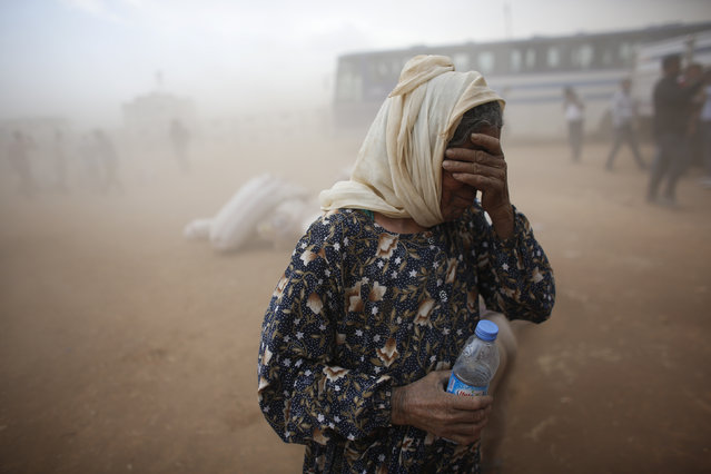 A Kurdish Syrian refugee covers her face as she waits for transport during a sand storm on the Turkish-Syrian border near Suruc in Sanliurfa province, Turkey September 24, 2014. (Photo by Murad Sezer/Reuters)