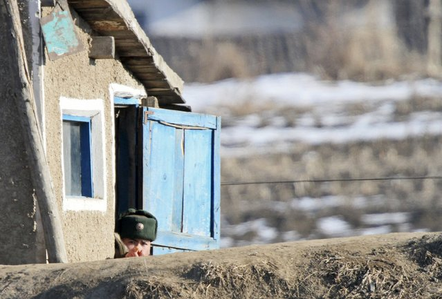 A North Korean soldier reacts as he is pictured in a guard tower on the banks of Yalu River, in Sakchu county, North Korea, January 7, 2016. (Photo by Jacky Chen/Reuters)
