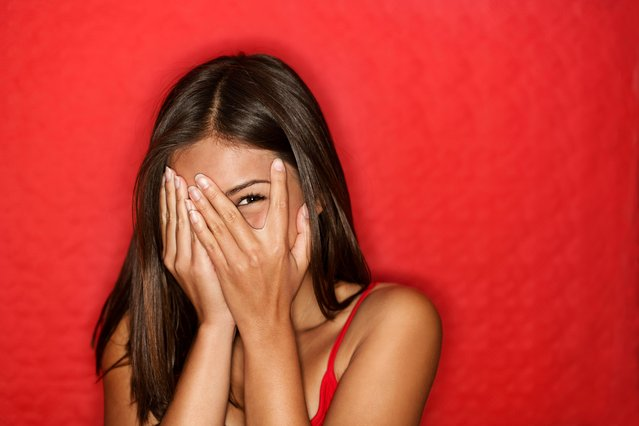 Playful shy woman hiding face laughing. (Photo by ariwasabi/Getty Images)