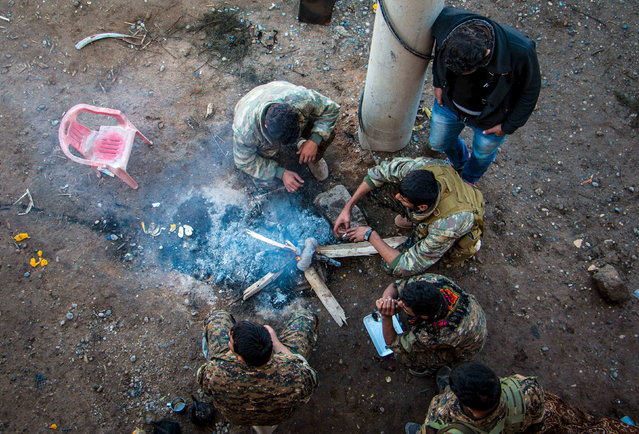 Rebel fighters from the Democratic Forces of Syria, gather around a fire near al-Hawl area where fighting between them and Islamic State fighters are taking place in south-eastern city of Hasaka, November 10, 2015. (Photo by Rodi Said/Reuters)