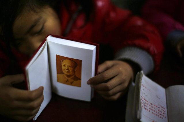 A student falls asleep as she holds a book containing a portrait of China's late chairman Mao Zedong during a lesson at the Democracy Elementary and Middle School in Sitong town, Henan province December 3, 2013. (Photo by Carlos Barria/Reuters)