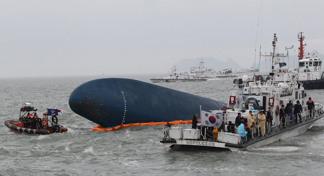 In this April 17, 2014 file photo, South Korean Coast Guard personnel search for missing passengers aboard the sunken South Korean ferry Sewol in the water off the southern coast near Jindo, South Korea. High school student Cho Eun-hwa, 16, was one of 304 people killed one year ago on Thursday, April 16 in the sinking of the ferry, and among nine whose bodies still have not been recovered. (Photo by Ahn Young-joon/AP Photo)