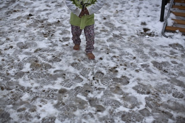 "A Syrian refugee child walks barefoot on frozen ground at the refugee camp of Ritsona about 86 kilometers (53 miles) north of Athens, Wednesday, January 11, 2017. The European Commission said conditions for refugees on islands and other camps where they are housed in tents despite severe cold weather, is ""untenable"". (Photo by Muhammed Muheisen/AP Photo)"