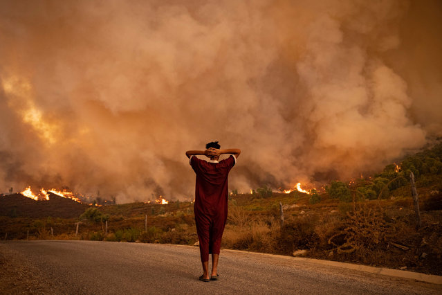 A woman looks at wildfires tearing through a forest in the region of Chefchaouen in northern Morocco on August 15, 2021. Firefighters were battling overnight to put out two forest blazes, a forestries official said as the North African kingdom swelters in a heatwave that saw temperatures of up to 49 degrees Celsius (120 Fahrenheit) on the weekend, according to weather authorities. Morocco joins several other Mediterranean countries that have seen forest fires in recent weeks, including neighbouring Algeria where at least 90 people were killed in wildfires last week. (Photo by Fadel Senna/AFP Photo)