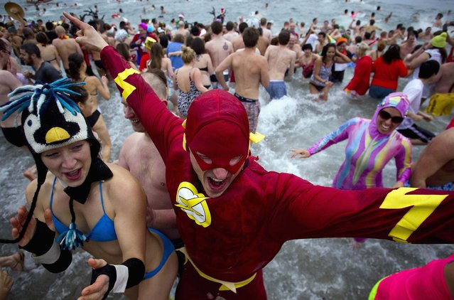 Participants run into English Bay during the 94th annual New Year's Day Polar Bear Swim in Vancouver, British Columbia. (Photo by Ben Nelms/Reuters)