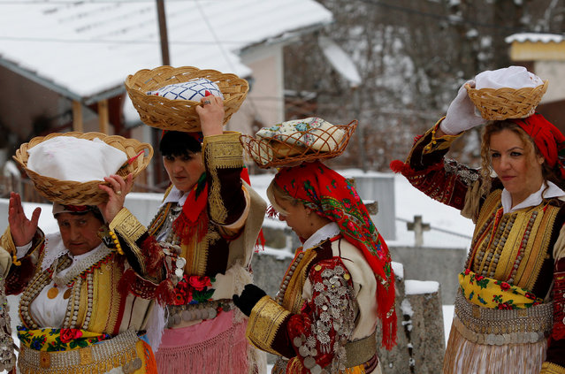 Women dressed in traditional folk costumes participate at the Epiphany day celebration in Bitushe, Macedonia January 19, 2017. (Photo by Ognen Teofilovski/Reuters)