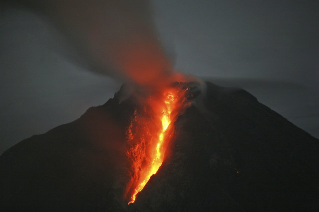 In this late Sunday, January 5, 2014 photo, Mount Sinabung spews hot lava as seen from Jeraya, North Sumatra, Indonesia. The 2,600-meter (8,530-foot) volcano has sporadically erupted since September. Authorities extended a danger zone around a rumbling volcano in western Indonesia on Sunday after it spewed blistering gas farther than expected, sending panicked residents streaming down the sides of the mountain. (Photo by Binsar Bakkara/AP Photo)