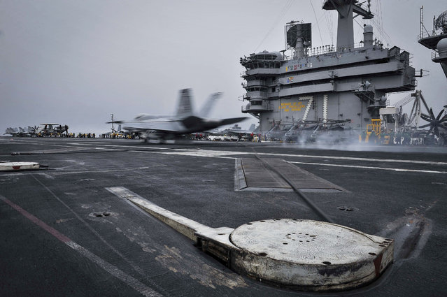 In this Wednesday, April 15, 2015 image released by U.S. Navy Media Content Services, an F/A-18E Super Hornet, assigned to the Knighthawks of Strike Fighter Attack Squadron 136, lands on the flight deck aboard Nimitz-class aircraft carrier USS Theodore Roosevelt in the Fifth Fleet area of operations. (Photo by Mass Communication Specialist Seaman Anna Van Nuys/U.S. Navy Media Content Services via AP Photo)