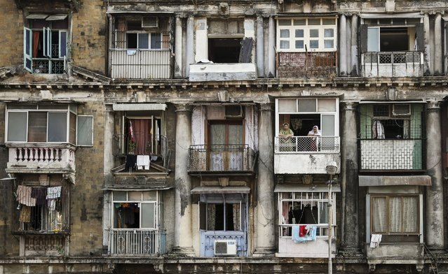 Residents look out of a window of an apartment in south Mumbai February 19, 2014. The cost for buying a 600 square feet (55 square meters) one-bedroom apartment in this building is around 14,166 Indian rupees ($225) per square feet or 8,500,000 Indian rupees ($136,000). The rent for an apartment in the same building is around 20,000 Indian rupees ($320) per month. (Photo by Danish Siddiqui/Reuters)
