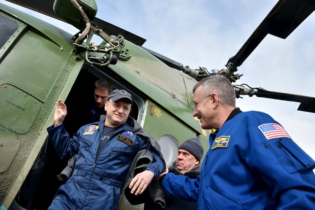 Members of NASA support team help International Space Station (ISS) crew member astronaut Scott Kelly of the U.S. to get off a helicopter, who arrived from the landing site to an airport in Dzhezkazgan (Zhezkazgan), Kazakhstan, March 2, 2016. (Photo by Kirill Kudryavtsev/Reuters)