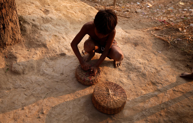 A boy closes a snake pot in Jogi Dera (snake charmers settlement), in the village Baghpur, in the central state of Uttar Pradesh, India November 9, 2016. (Photo by Adnan Abidi/Reuters)